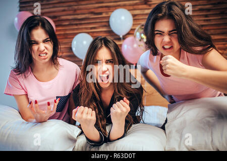 Emotionale junger Frauen auf Kamera. Sie sitzen auf dem Bett mit verärgerten Gesichter. Mädchen sind sehr emotionale - Stockfoto