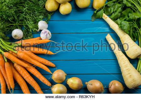 Grenze der sortierten frischem gesunden Gemüse auf einem urigen Bauernhof blau Holz Hintergrund mit zentralen Kopie Platz in einer Ansicht von oben - Stockfoto
