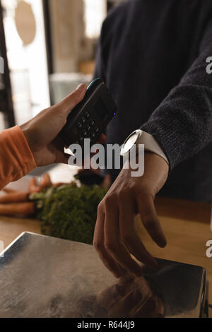 Kunden die Zahlung durch smartwatch am Zähler - Stockfoto