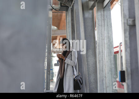 Frau mit Handy in der Plattform - Stockfoto