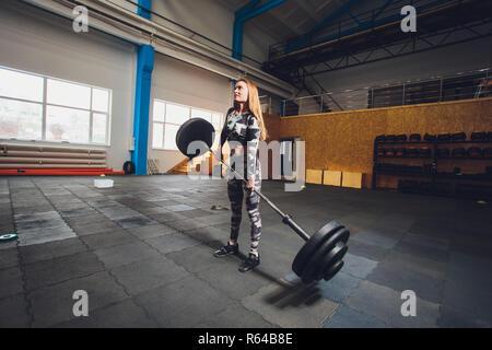 Attraktive junge Sport Frau mit Barbell. Deadlift. ließ die Kurzhanteln, fällt die Hanteln auf den Boden - Stockfoto