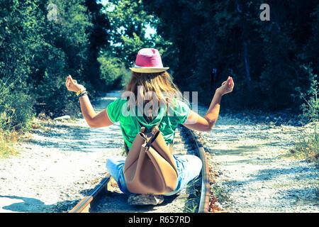 Eine Frau sitzend mit zurück auf den Bahngleisen und Yoga. - Stockfoto