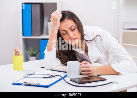 Müde Frau Doktor ist schlafen und Kaffee trinken, während in Ihrem Büro arbeiten