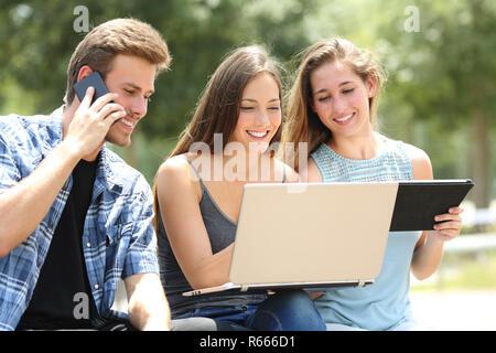 Drei glückliche Freunde mit mehreren Geräten sitzen auf einer Bank in einem Park - Stockfoto