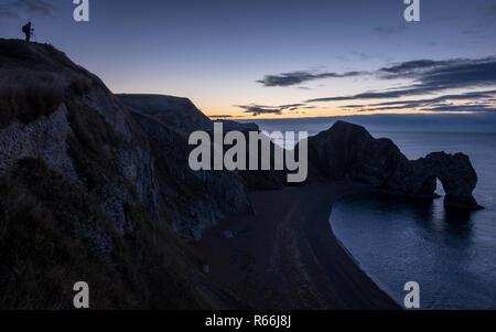 Ein Fotograf seine Kamera vorbereiten für den Sonnenaufgang über Durdle Door auf in Dorset Jurassic Coast