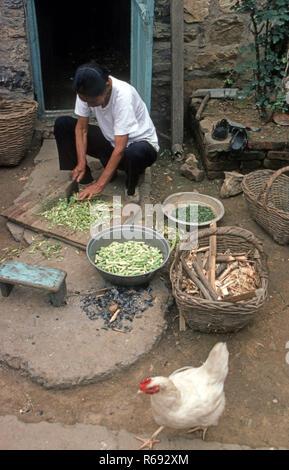 Northern China 1980 Gemeinde im Waoning Provinz, wo eine Frau hockt außerhalb der Vorbereitung Gemüse für eine Mahlzeit - Stockfoto