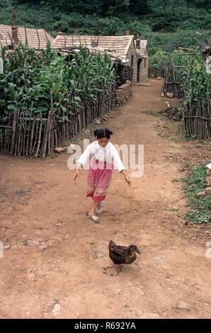 Northern China 1980 Gemeinde im Waoning Provinz mit Häusern aus Stein, in denen junge Mädchen jagt eine Ente - Stockfoto