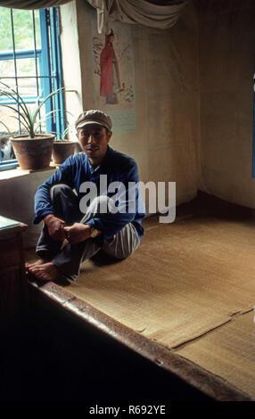 Northern China 1980 Gemeinde im Waoning Provinz in einem Innenraum von einem Haus, in dem ein Mann saß auf einem Kang ein Bett Herd, eine Plattform aus Ziegeln, wo geschleust, die durch ein Feuer Wärme, die normalerweise Holz Feuer angefacht wird. - Stockfoto