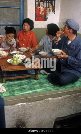 Northern China 1980 Gemeinde im Waoning Provinz in einem Innenraum von einem Haus, in dem eine Familie essen Essen sitzen auf einem Kang ein Bett Herd, eine Plattform aus Ziegeln, wo geschleust, die durch ein Feuer Wärme, die normalerweise Holz Feuer gespeist wird. - Stockfoto
