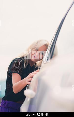 Fröhlicher junger weiblicher Treiber Ihr neues Auto umarmte. - Stockfoto
