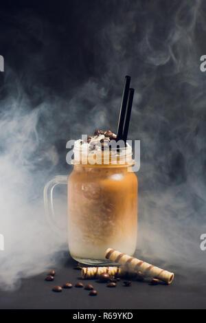 Iced Caramel latte Kaffee in hohen Glas mit Sirup und Sahne. Rauch - Stockfoto