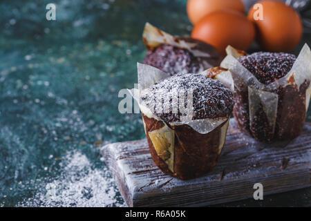 Karotte - chocolate Muffin bestäubt mit Puderzucker, eine Tasse Tee, Backzutaten. Mehl, Eier, Zitrone auf einem dunklen Raum Tabelle kopieren Stockfoto