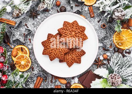 Urlaub Backen Hintergrund. Weihnachten Lebkuchen cookies mit Messer und Gewürzen auf grauem Beton Tabelle. Weihnachten essen. Ansicht von oben.