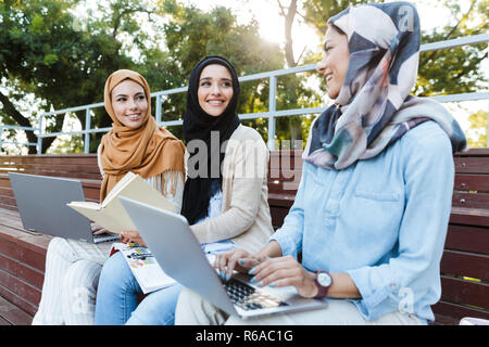 Foto der Schönen muslimischen Mädchen tragen headscarfs ruht im Green Park und Studieren auf Laptop - Stockfoto
