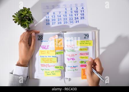Geschäftsfrau Hand mit Kalender Schreiben Zeitplan im Tagebuch - Stockfoto