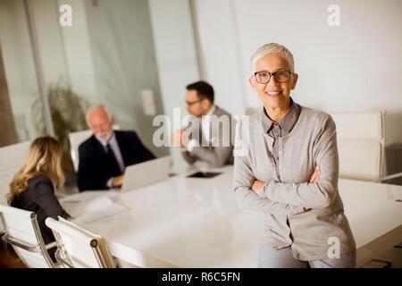 Portrait von fröhlichen senior Geschäftsfrau im Büro, während andere Geschäftsleute in Sitzung - Stockfoto