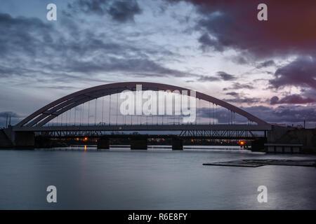 Eisenbahnbrücke über den Fluss Wisla Martwa bei Dämmerung in Danzig. Polen Europa. - Stockfoto