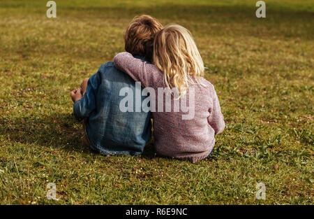 Hintere Aufnahme des Geschwister sitzen auf dem Gras. Kleines Mädchen sitzt mit ihrem Bruder, ihren Arm auf seiner Schulter im Park. - Stockfoto