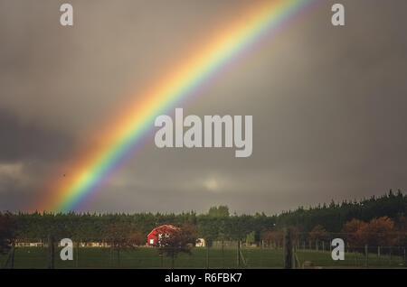 Voller Regenbogen über der Farm in Neuseeland - Stockfoto