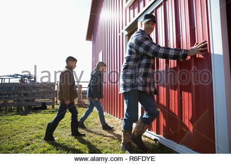Landwirt und Söhne öffnen Stalltür an sonnigen Hof - Stockfoto