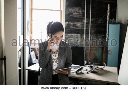 Kreative Geschäftsfrau mit Smart Phone und Verwendung digitaler Tablette im Büro - Stockfoto
