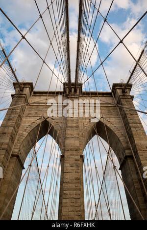 Malerische abstrakte Sicht der Stahlseile und texturierte Steine der ikonischen stone arch Tower der Brooklyn Bridge unter blauen Himmel bei Sonnenuntergang - Stockfoto