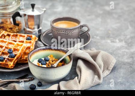 Frühstück mit Müsli, Joghurt, frischem hausgemachten belgischen Waffeln und heiße Tasse schwarzen Kaffee - Stockfoto