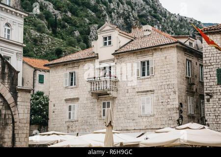 Die Fassade eines gewöhnlichen alten Gebäude mit Fenstern und einem Balkon in Montenegro. Traditionelle Gehäuse. Im Hintergrund ist ein Berg. Auf das Gebäude ist die Flagge von Montenegro. - Stockfoto