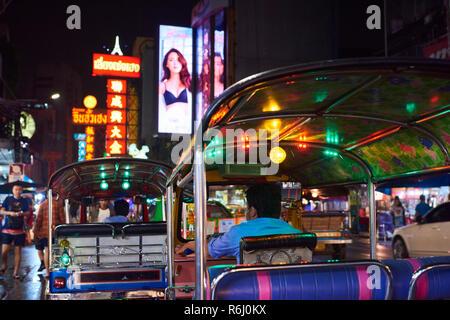 Night Shot der traditionelle bunte Tuk-Tuk Motorrad in Chinatown in Bangkok, Thailand, mit Leuchtreklamen im Hintergrund. - Stockfoto