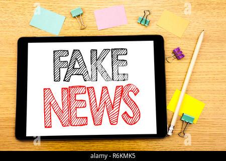 Schreiben Text anzeigen gefälschte Nachrichten. Business Konzept für Hoax Journalismus auf Tablet Notebook geschrieben, Holz- Hintergrund mit Haftnotiz und Stift