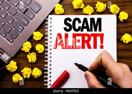 Konzeptionelle Hand schreiben Bildunterschrift Scam Alert. Business Konzept für Betrug Warnung auf Tablet Notebook geschrieben, Holz- Hintergrund mit Geschäftsmann, Hand, Finger, PC. - Stockfoto