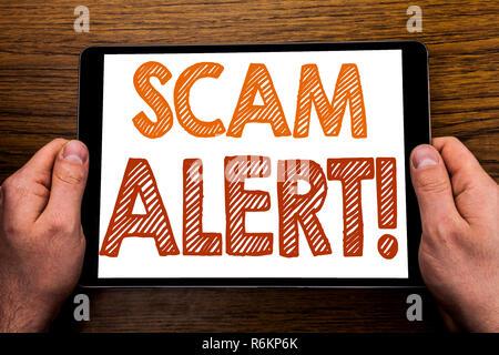 Hand schreiben Bildunterschrift Scam Alert. Business Konzept für Betrug Warnung auf Tablet Notebook geschrieben, Holz- Hintergrund mit Geschäftsmann, Hand, Finger, PC. - Stockfoto