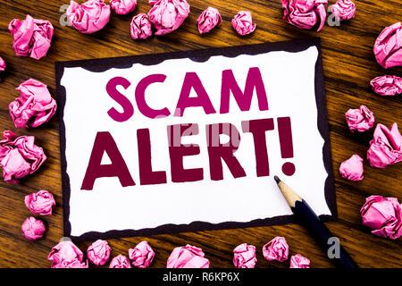 Hand schreiben Bildunterschrift Inspiration übersicht scam Alert. Business Konzept für Betrug Warnung auf haftnotiz Papier, Holz- Hintergrund mit gefalteten rosa Papier Sinne denken - Stockfoto