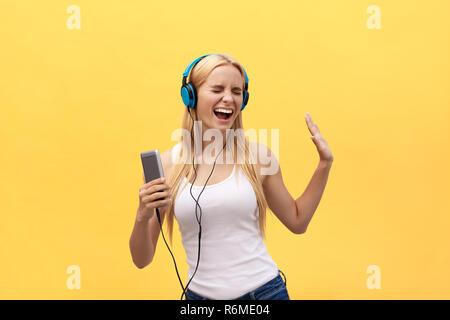 Lifestyle Portrait einer Frau hören Musik im Kopfhörer auf gelbem Hintergrund - Stockfoto