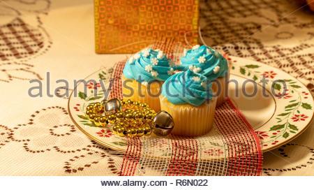 Serie der Blauen Frosted Cupcakes arrangiert mit festlichen Dekorationen - Stockfoto