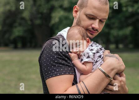 Junger Vater außerhalb schaukelnd seine niedlichen Baby Boy - Stockfoto