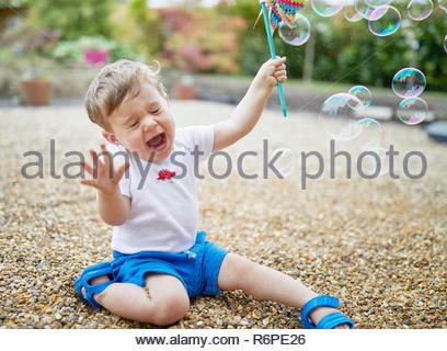 Kleinkind spielen draußen mit Blasen zu lächeln und zu lachen - Stockfoto