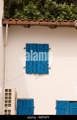 Blauen Jalousien geschlossen Fenster auf eine beige Wand. - Stockfoto