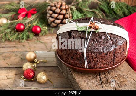 Chocolate Christmas Pudding serviert auf Platte mit Weihnachten Dekorationen. Holz- Hintergrund. - Stockfoto