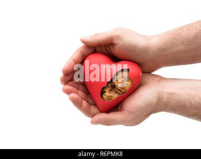 Rotes Herz mit goldenen Münzen in die Hände über weißen Hintergrund mit Freistellungspfad - Stockfoto