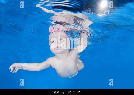 5 Monate Kleinkind Mädchen unter Wasser in Waterbaby Klasse im Pool schwimmen lernen - Stockfoto