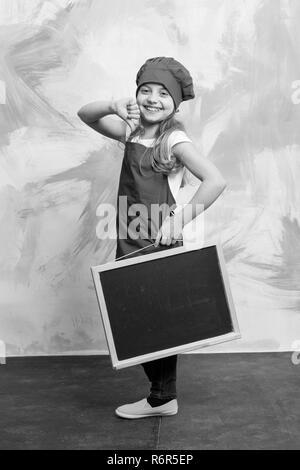 Kid oder glückliche kleine Mädchen kochen in rot Chef hat und Schürze halten Menü Blackboard auf farbigen Hintergrund, Kochen und Essen, kopieren Raum - Stockfoto