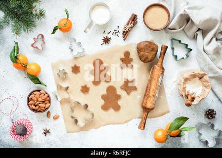 Vorbereitung von Lebkuchen Cookies. Ungebackene Lebkuchen cookies und Plätzchenteig auf Pergamentpapier mit Weihnachtsschmuck um. Ansicht von oben, flach - Stockfoto