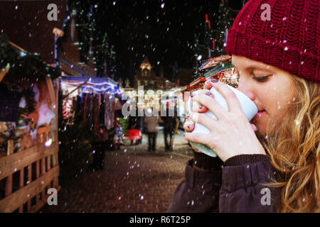Junge Frau trinkt ein warmes Getränk auf dem Weihnachtsmarkt - Stockfoto