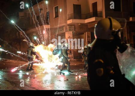 Eine Tankstelle gesehen, explodierende Bombe neben der Polizei bei den Ausschreitungen auf der Exarchia Platz in Athen nach dem Protest der 10. Jahrestag des Todes der 15-jährigen Alexis Grigoropoulos durch Polizeikugel getötet, nachdem einige Offiziere eine Gruppe von Jungen angefahren und angeblich provoziert sie. - Stockfoto