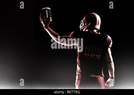 Spotlight gegen American football player im Helm Holding rugby ball - Stockfoto