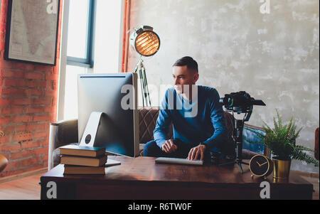 Stabilisator Kamera. Computer überwachen. Junge Freiberufler mann Videobearbeitung auf Laptop für das Hochladen von Videos auf Internet online oder Social Media.