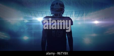 American football player im Helm gegen American football arena stehend - Stockfoto