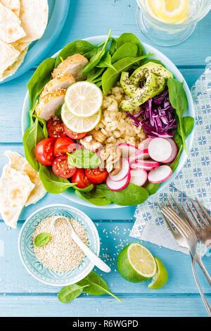 Schüssel mit gegrilltem Hähnchenfleisch, Bulgur und frisches Gemüse Salat, Radieschen, Tomaten, Avocado, Grünkohl und Spinat. Gesund und lecker Sommer