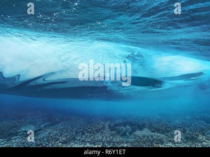 Surfer Schneiden durch eine Welle über das Riff in Malediven - Stockfoto